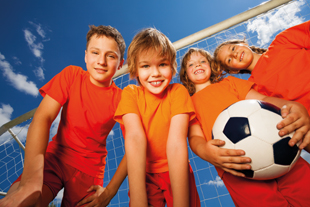 Four happy kids in orange T-shirt portrait from below with football